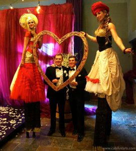 stilt walkers at wedding with big love heart frame photo experience- by www.catalystarts.com